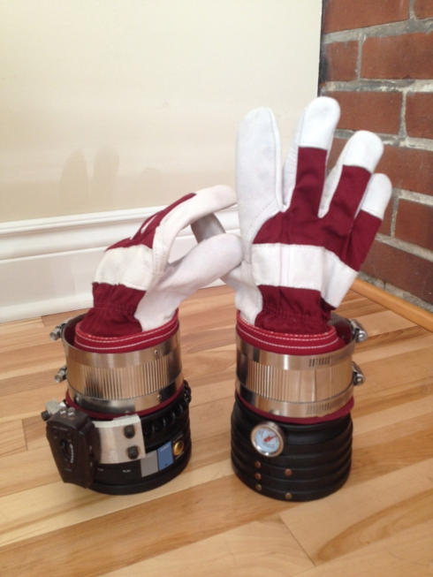 Workman gloves and plumbing parts, with a BBQ thermometer and video remote buttons.
